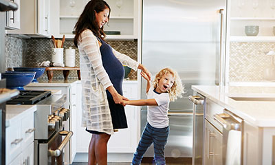 Pregnant woman and child playing in kitchen.