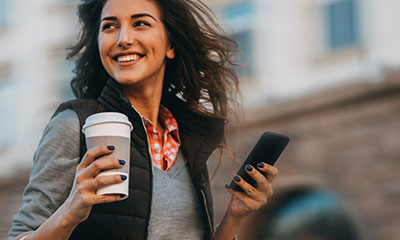 Women walking in public holding her phone and cup of coffee.