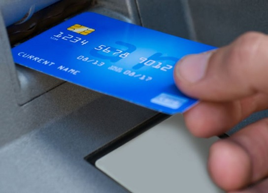 Photo of a Debit card being inserted into an ATM