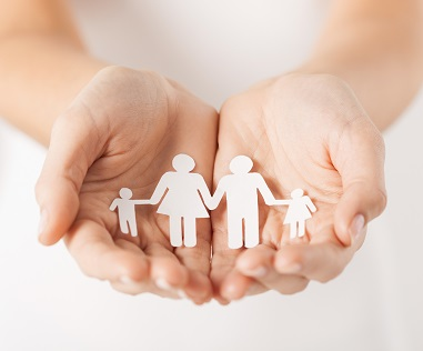Picture of outstretched hands with a paper cutout of a family in them.